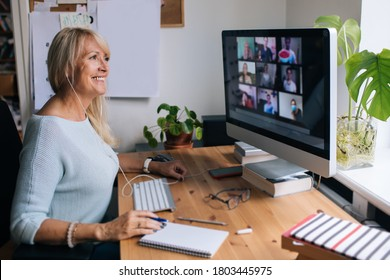 Smiling mature woman having video call via computer in the home office. Online team meeting video conference calling from home. Attractive Businesswoman Telework. Business video conferencing.