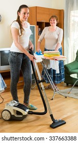 Smiling mature woman and her adult daughter cleaning together at home