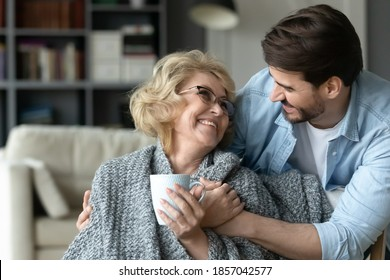 Smiling mature woman holding cup, hugging with adult son close up, enjoying leisure time, happy elderly mother wearing warm scarf drinking hot tea or coffee, family spending weekend together at home