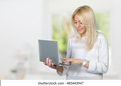 Smiling mature woman holding laptop