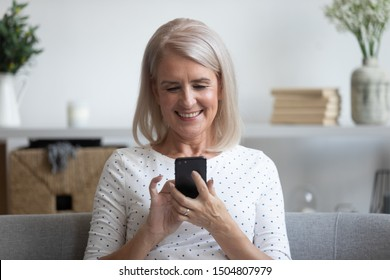 Smiling mature woman holding phone, using mobile device apps, looking at screen, happy older female chatting online, texting, writing message on cellphone, having fun at home, sitting on couch