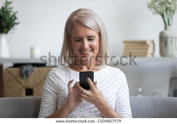Lächelnde reife Frau, die ein Telefon hält, Mobiltelefon-Apps verwendet, Bildschirm anschaut, glückliche ältere Frau, die online chattet, SMS schreibt, Nachrichten auf dem Handy schreibt, sich zu Hause amüsiert, auf dem Sofa sitzt