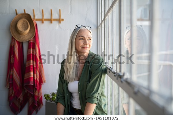 Smiling mature woman looking outside window. Thoughtful old woman looking away through window. Senior beautiful woman sitting at home with pensive expression.