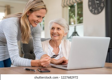 Smiling mature woman making payment via credit card for shopping done by senior woman at home. Elderly mother and daughter buying online. Family generations using laptop computer paying bills.