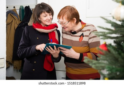 Smiling mature woman participating in survey conducted at home by polite social female worker