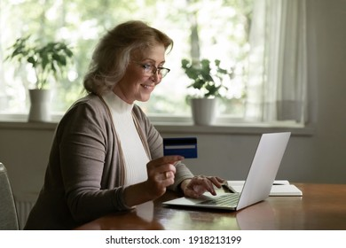 Smiling mature woman paying online by credit card, using laptop, looking at screen, happy satisfied elderly customer shopping, browsing internet banking service, checking balance, secure payment