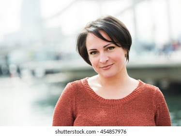 Smiling  mature woman posing outdoors in sunny day