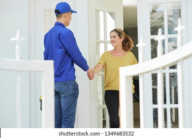 Smiling mature woman shaking hands with repairman in uniform while he standing outdoor near her house