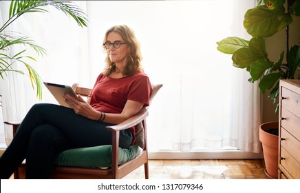 Smiling mature woman sitting in a chair in her sunny home browsing the internet with a digital tablet