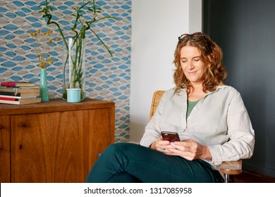 Smiling mature woman sitting in a chair in her stylish apartment sending a text message on a cellphone
