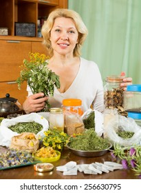 Smiling  mature woman sitting at  table with dried herbs in home