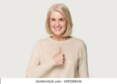 Smiling mature woman in sweater isolated on grey studio background show thumbs up recommend service, happy positive senior lady give sincere recommendation, advice good or sale offer
