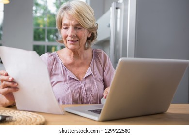 Smiling mature woman using her laptop and reading a file