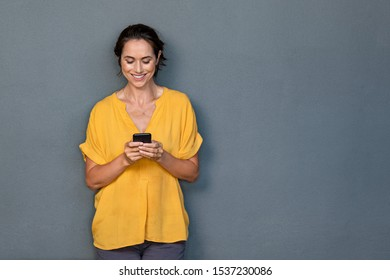 Smiling mature woman using smartphone isolated on gray wall with copy space. Happy latin woman in casual typing on cellphone over grey background. Portrait of cheerful middle aged lady messaging.