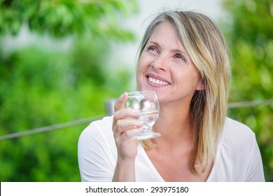 Smiling mature woman with water glass in her hands
