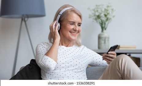 Smiling mature woman wear wireless headphone hold smartphone looking at phone screen using mobile player app listening online music, learning foreign language, watching video relaxing on sofa at home