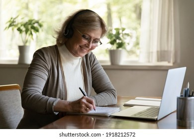 Smiling mature woman wearing headphones writing notes, using laptop, sitting at table at home, aged female wearing glasses listening to lecture, watching webinar, studying online, learning language