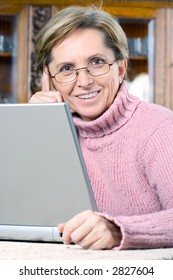 Smiling mature woman working on laptop in the living room.