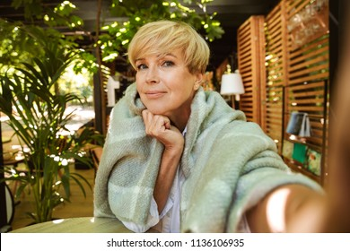 Smiling mature woman wrapped in blanket taking a selfie while sitting at a cafe