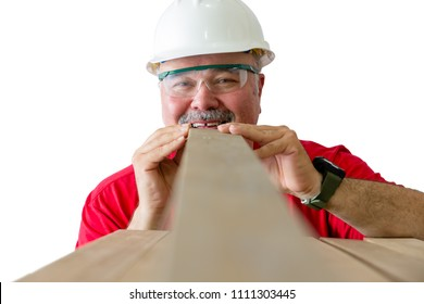 Smiling mature worker with helmet and safety glasses inspecting quality of wooden plank isolated against white background
