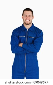 Smiling mechanic in boiler suit with folded arms against a white background