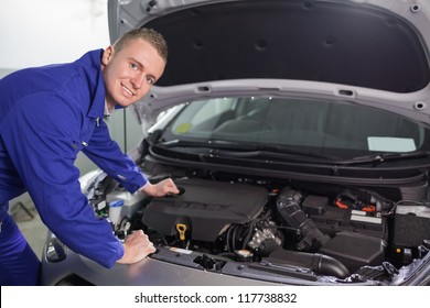 Smiling mechanic looking at camera in a garage