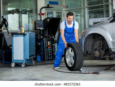 Smiling mechanic pushes the tire in a workshop