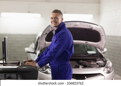 Smiling mechanic typing on a computer in a garage