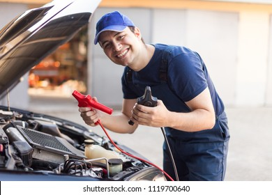 Smiling mechanic using cables to start a car engine