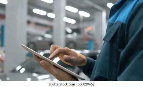 Smiling mechanic using a tablet pc at the repair garage service