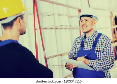 smiling mechanical engineer inspecting the work of labour at modern factory