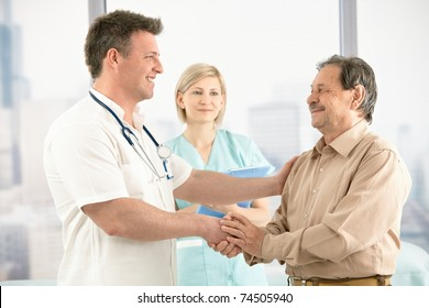 Smiling medical doctor shaking hands with happy senior patient, nurse in background.?