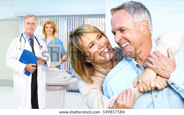 Smiling medical doctor with stethoscope and elderly couple.
