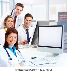 Smiling medical doctors with stethoscopes working with computer.