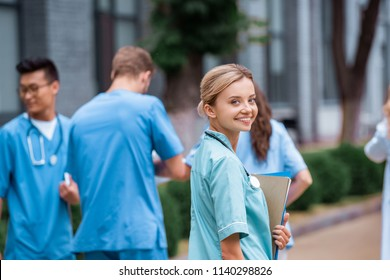 smiling medical student looking at camera on street near medical university