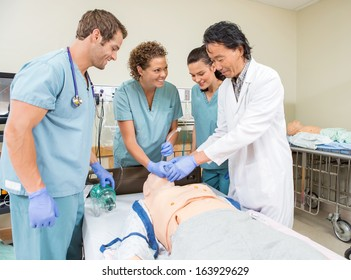 Smiling medical team adjusting endotracheal tube in dummy patient's mouth at hospital room