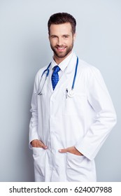 Smiling medical worker in white coat and blue tie holding his hands in pockets
