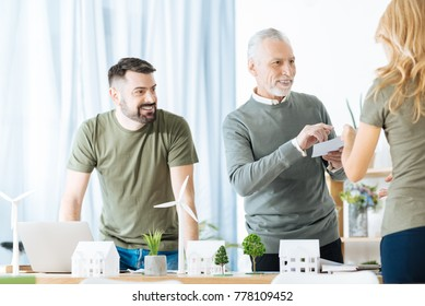 Smiling men. Positive friendly engineers standing near the table covered with tiny models of windmill turbines and smiling while looking at their colleague