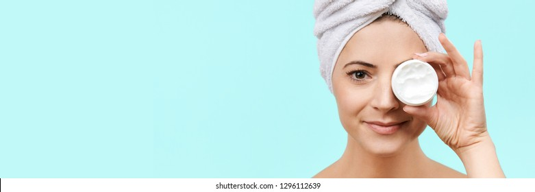 Smiling mid 30s woman holding moisturizing cream in front of her face. Photo of attractive caucasian woman with healthy skin isolated on pastel blue background. Beauty and Skincare concept.
