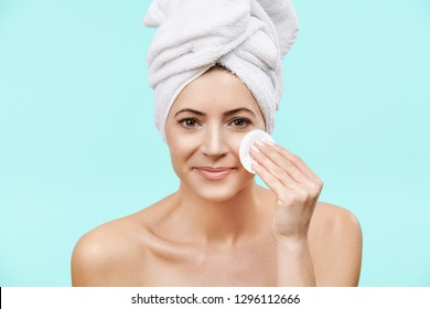 Smiling mid 30s woman removing make up using a cotton pad. Photo of attractive caucasian woman with healthy skin isolated on pastel blue background. Beauty and Skincare concept.
