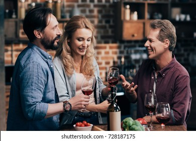 smiling mid adult friends drinking red wine and talking together at home
