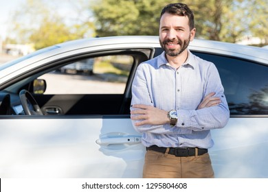 Smiling mid adult man making eye contact while standing arms crossed near white car