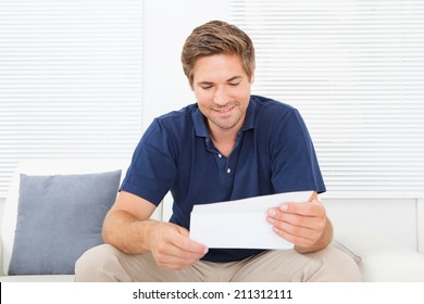 Smiling mid adult man reading letter while sitting on sofa at home