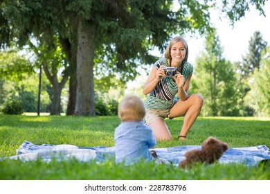 Smiling mid adult mother taking picture of baby boy in park