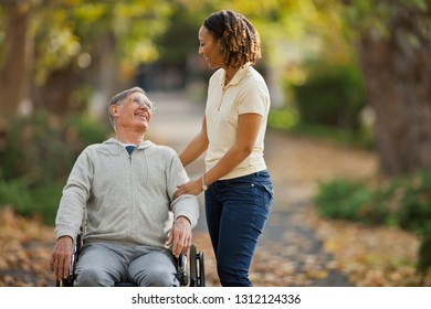 Smiling mid adult nurse assisting an elderly patient in a park.