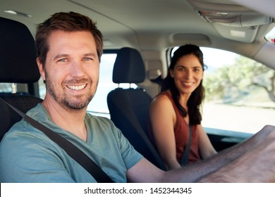 Smiling mid adult white couple driving in their car smiling to camera, close up, side view