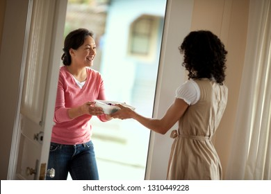 Smiling mid adult woman greeting her neighbor with a casserole dish.