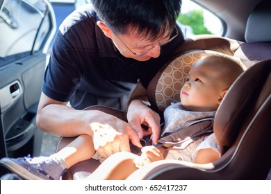 Smiling Middle age asian father helps his cute little asian 1 year old toddler baby boy child to fasten belt on car seat in car before driving, happy traveling with child concept