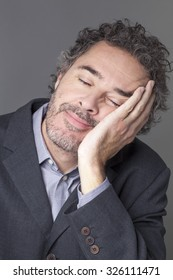 smiling middle age businessman closing his eyes,resting in leaning face on hand to sleep or nap for corporate break
