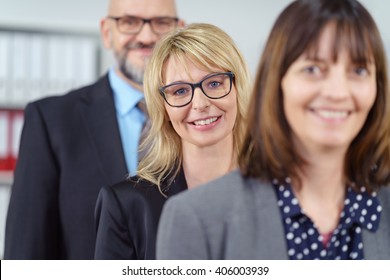 Smiling middle aged beautiful female business person wearing eyeglasses and blue jacket in focus between co-workers